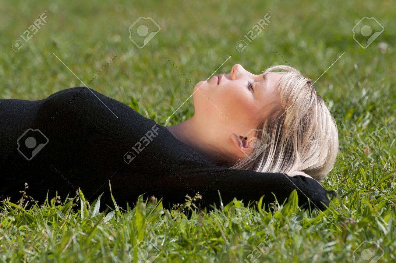 young woman lying on a meadow Stock Photo - 10978804