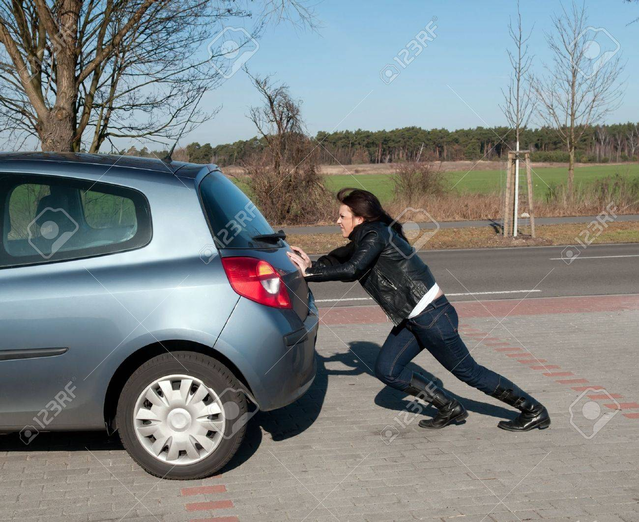 annoyed young woman pushes her car Stock Photo - 13107251