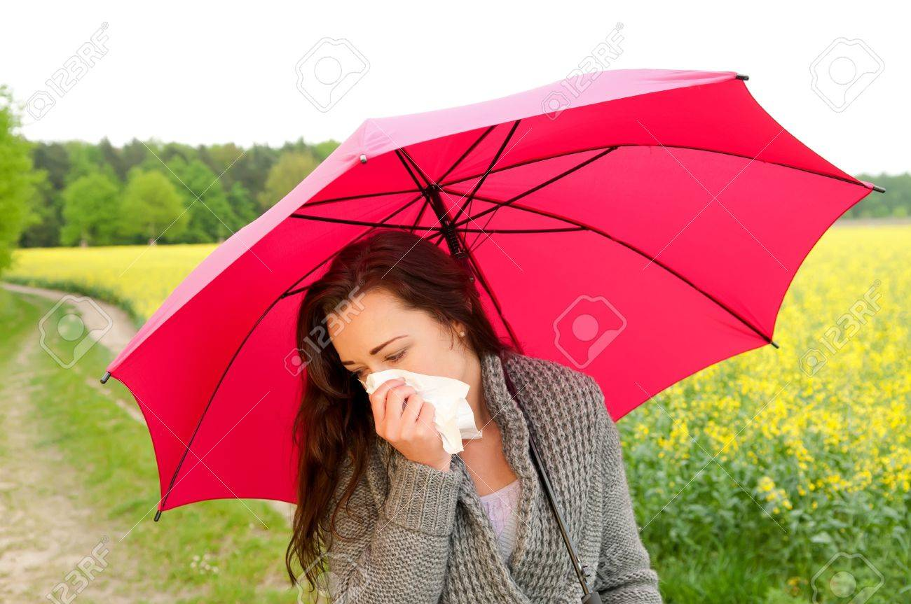young woman with red umbrella  has hay fever Stock Photo - 13859520
