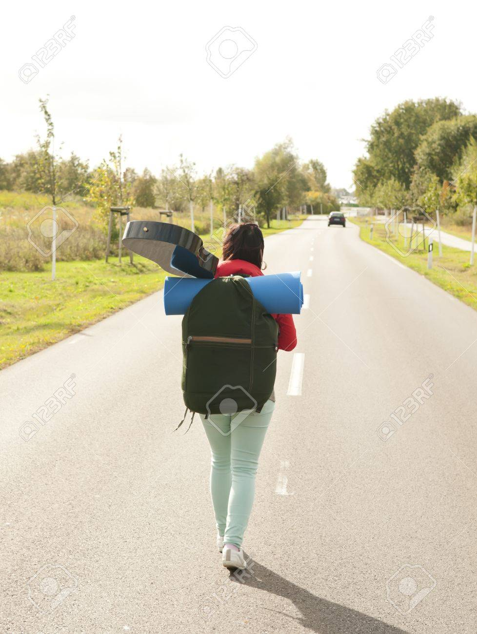 hitchhiker with guitar on the road, rear view Stock Photo - 15782034