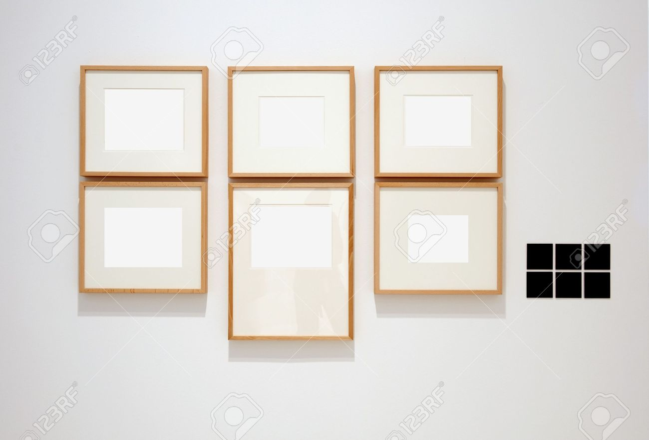 six empty frames on white wall in museum with labels stock photo 7102202