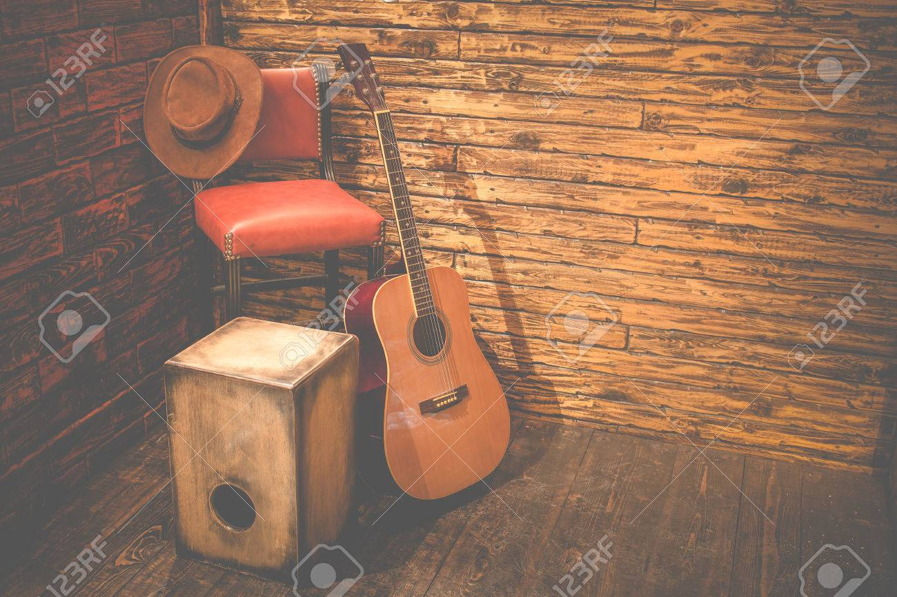 Cajon And Acoustic Guitar On Wooden Stage In Pub Stock Photo