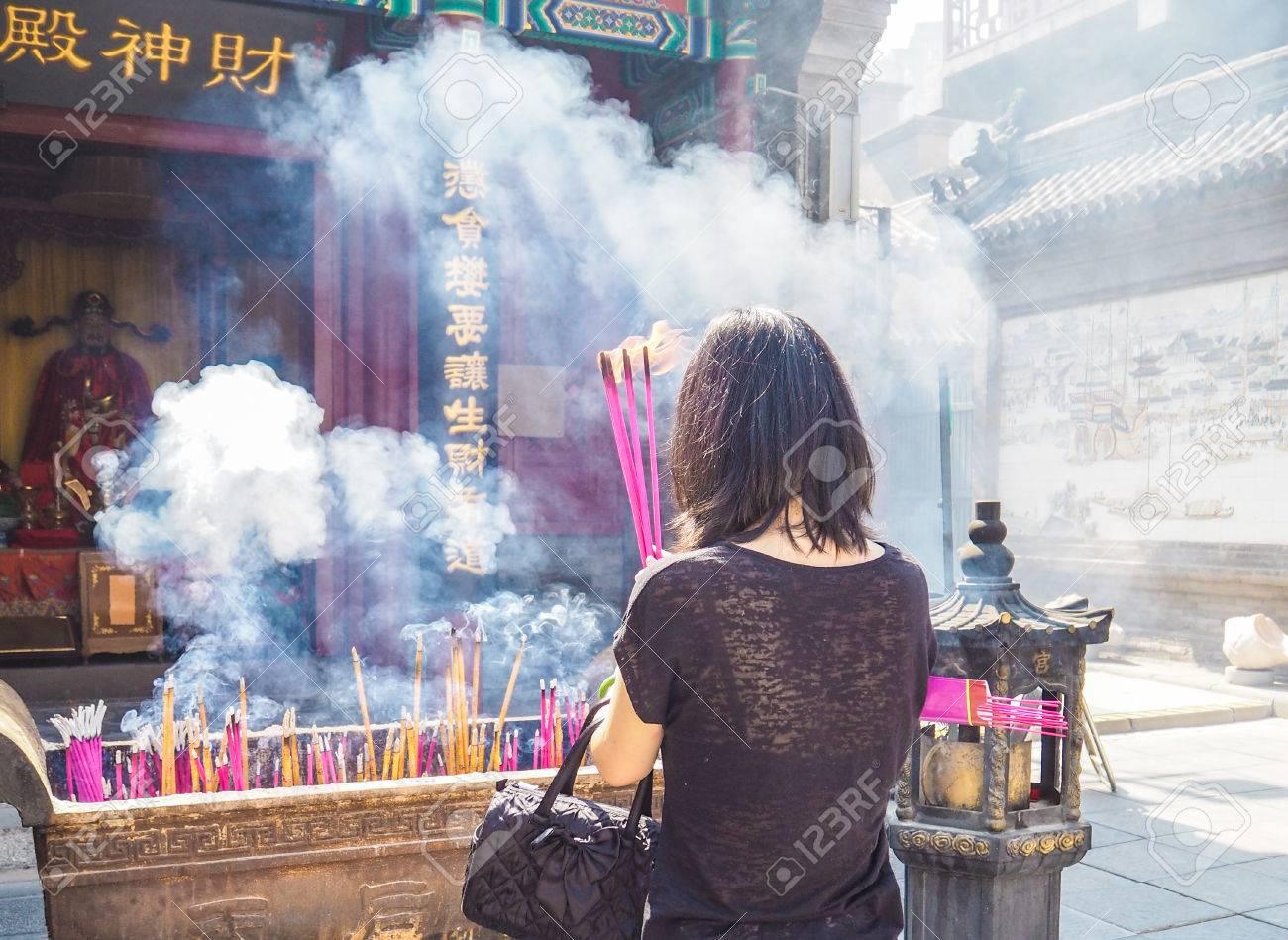 Young woman holding large burning incense sticks while praying