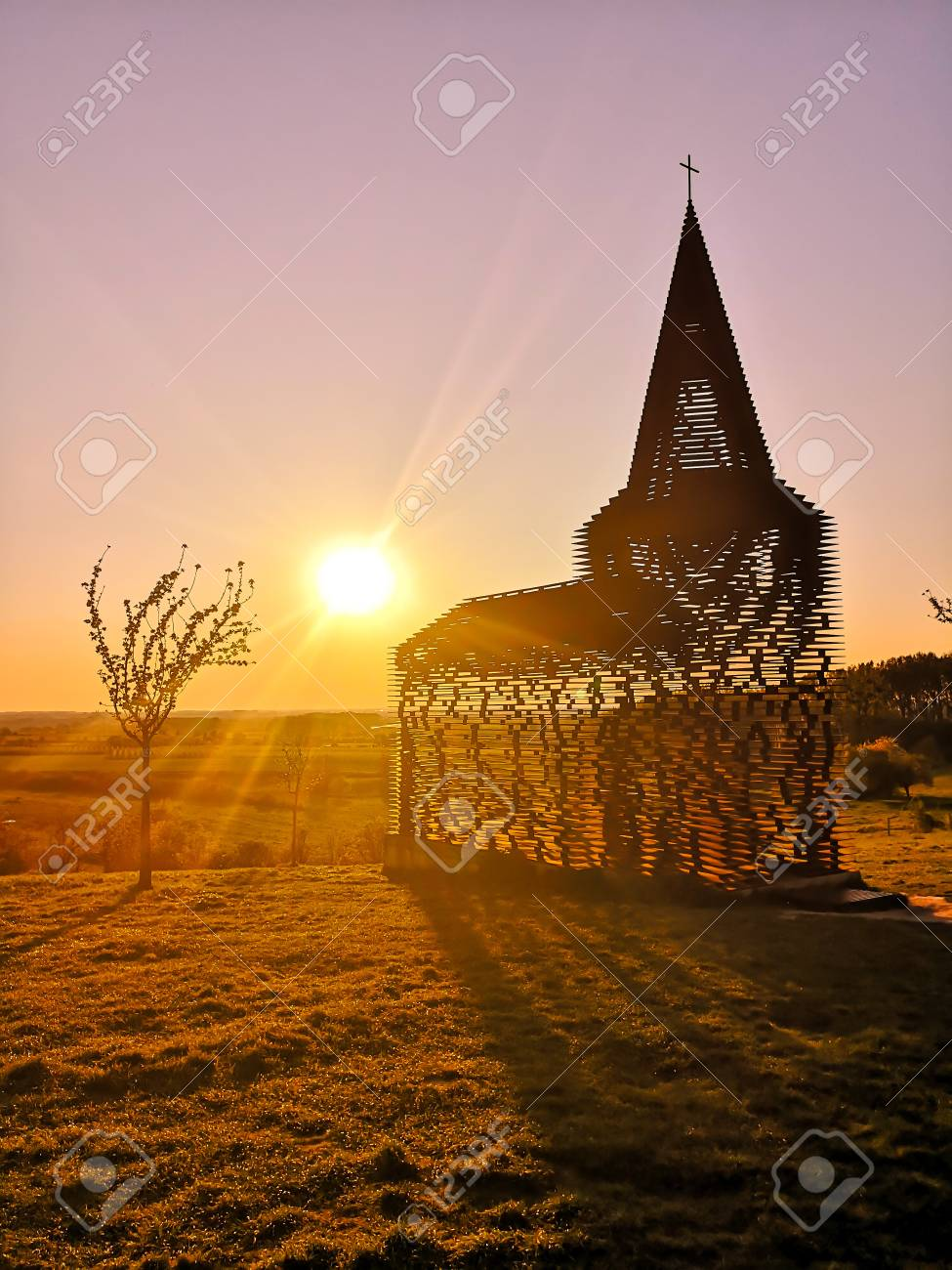 Steel see-through church in Borgloon (Hesbaye, Belgium), known as the art project Reading between the lines, during sunset - 126467860