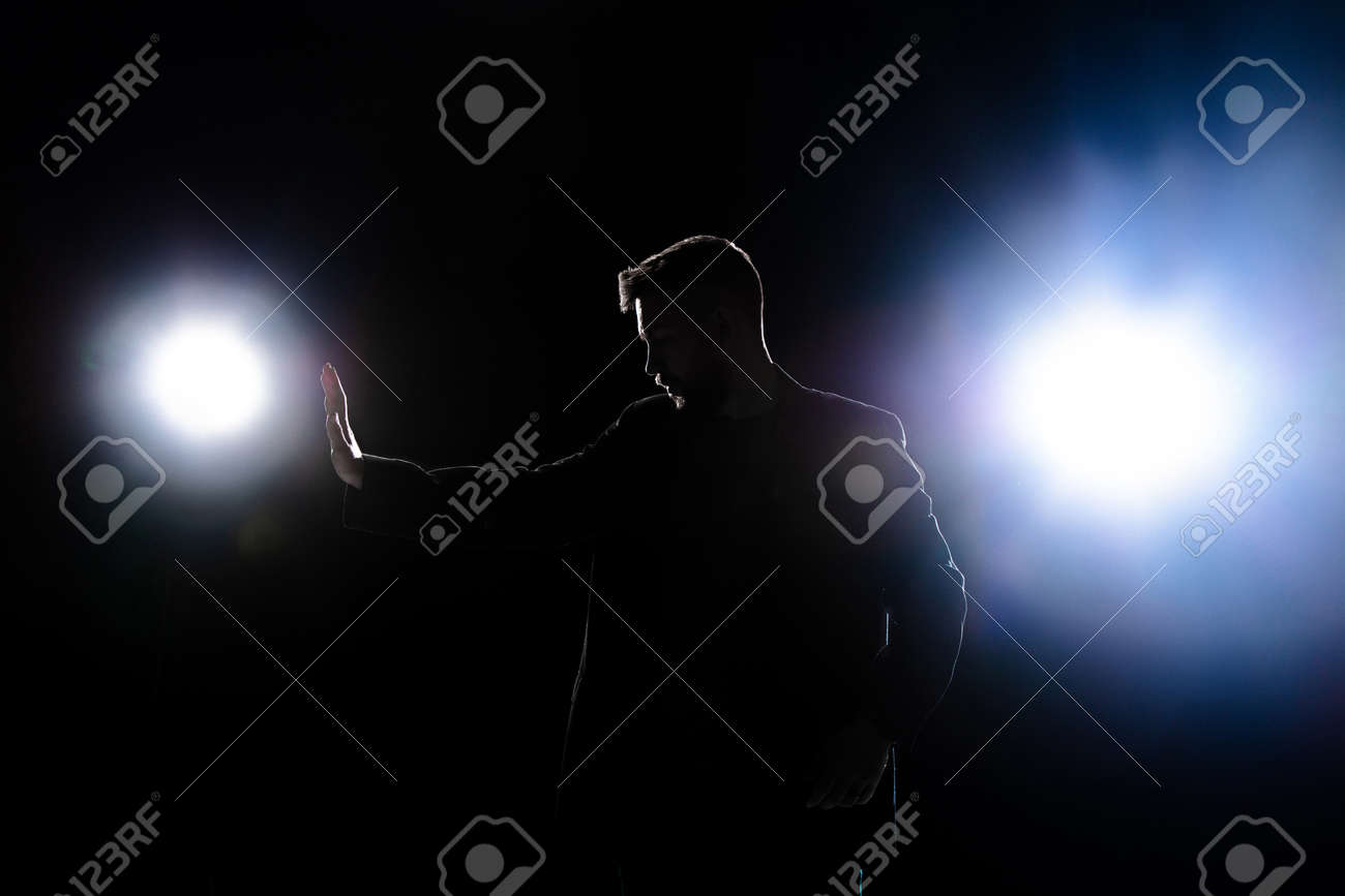 Silhouette of man protect himself isolated on dark background in lanterns light - 161167226