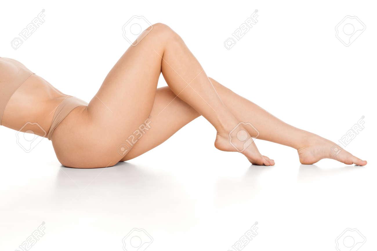 Beautiful slender tanned female legs in underwear over white background. - 167289798