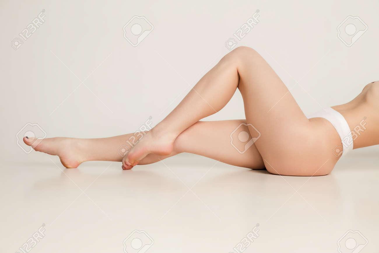 Beautiful slender tanned female legs in underwear over white background. - 168027647