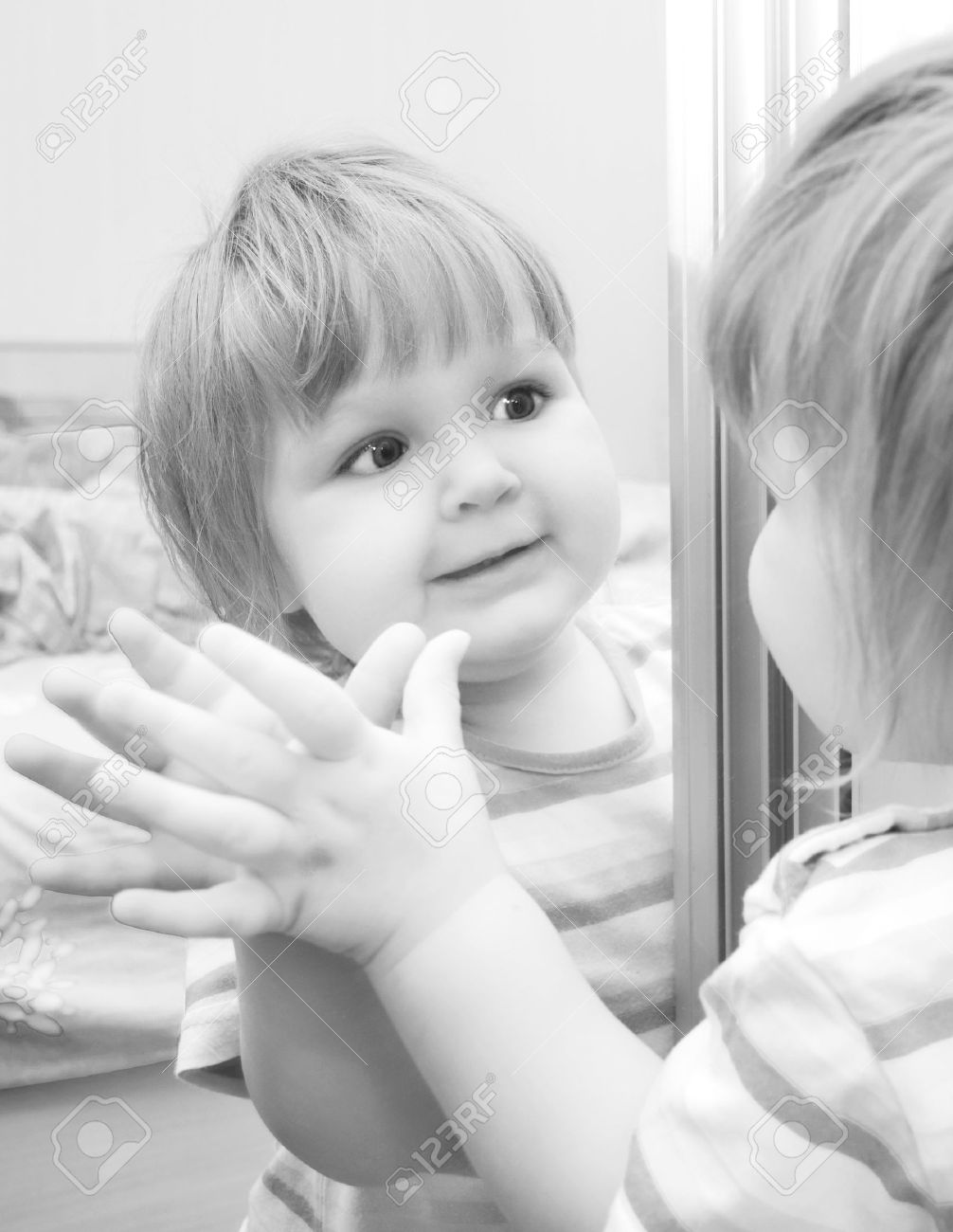 A girl looks in the mirror. Black and White image of baby. Stock Photo - 10861716