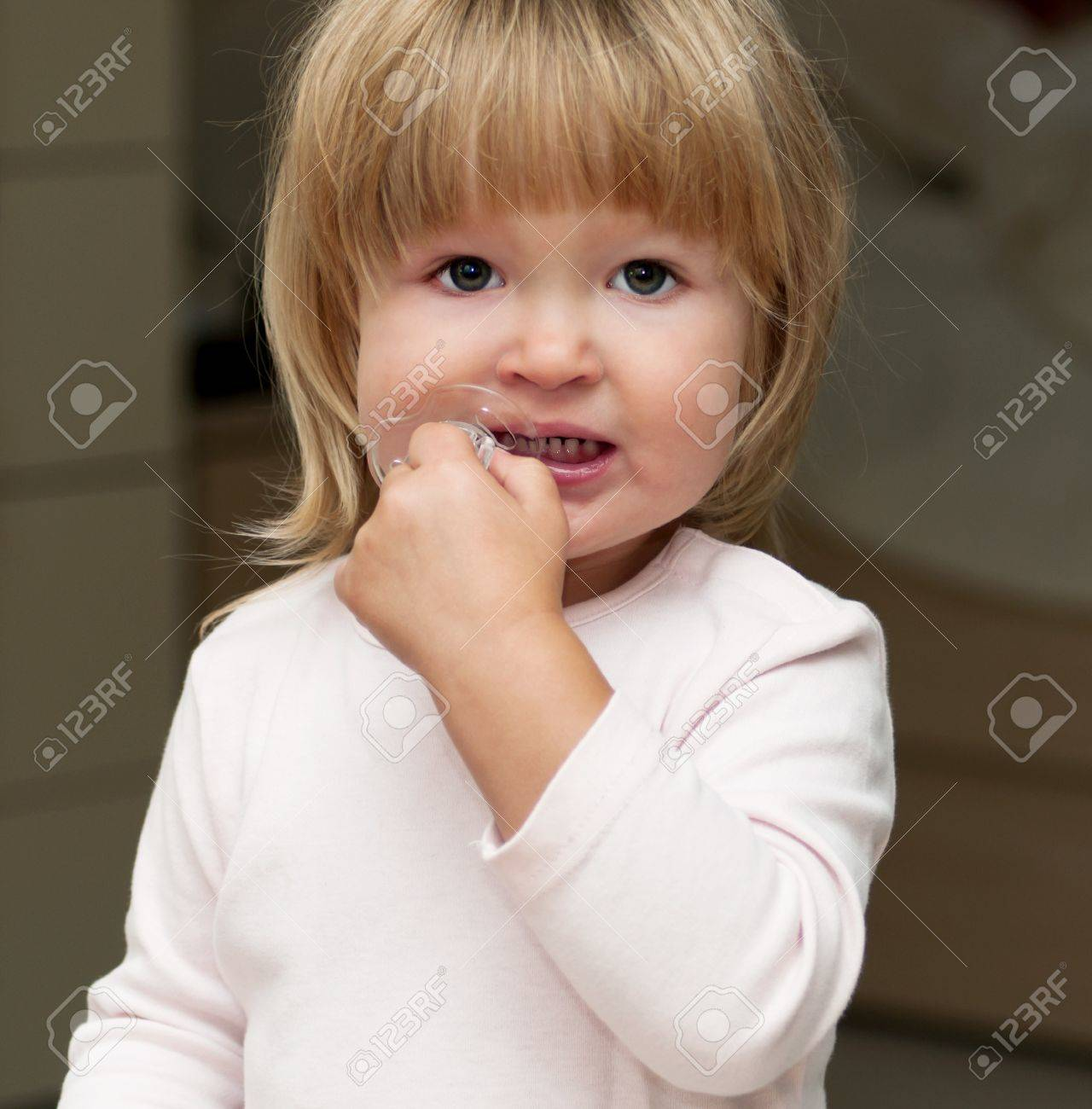 Little girl chewing on pacifier - 13144398