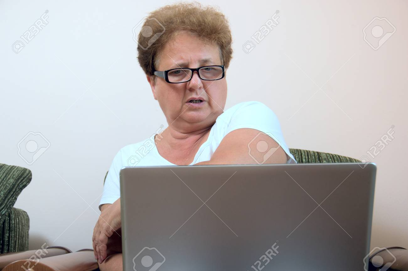 92b5c4dbaf old woman looks frightened at the laptop screen. Grandmother does not  understand how to use