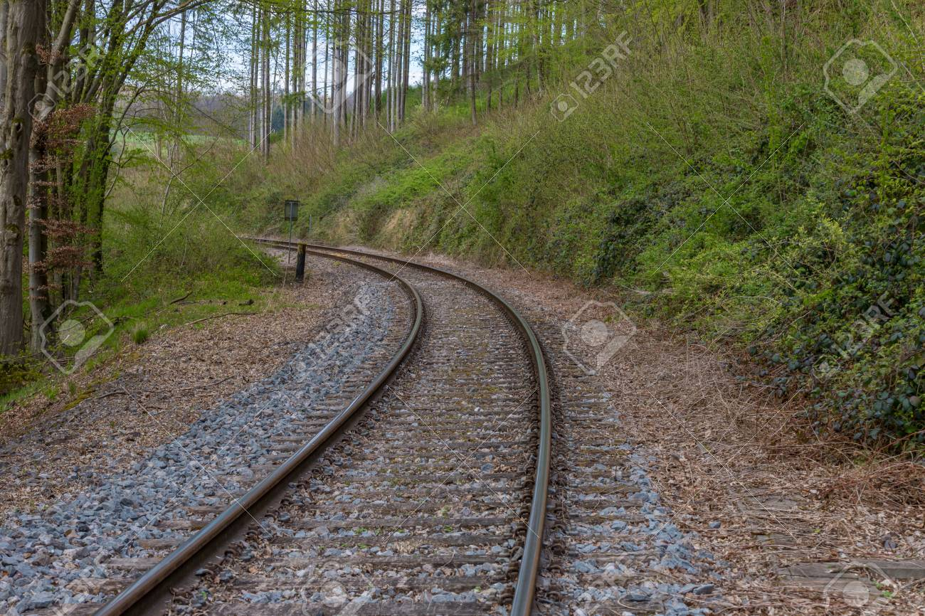 Train track in the middle of a european forest with stones, dry