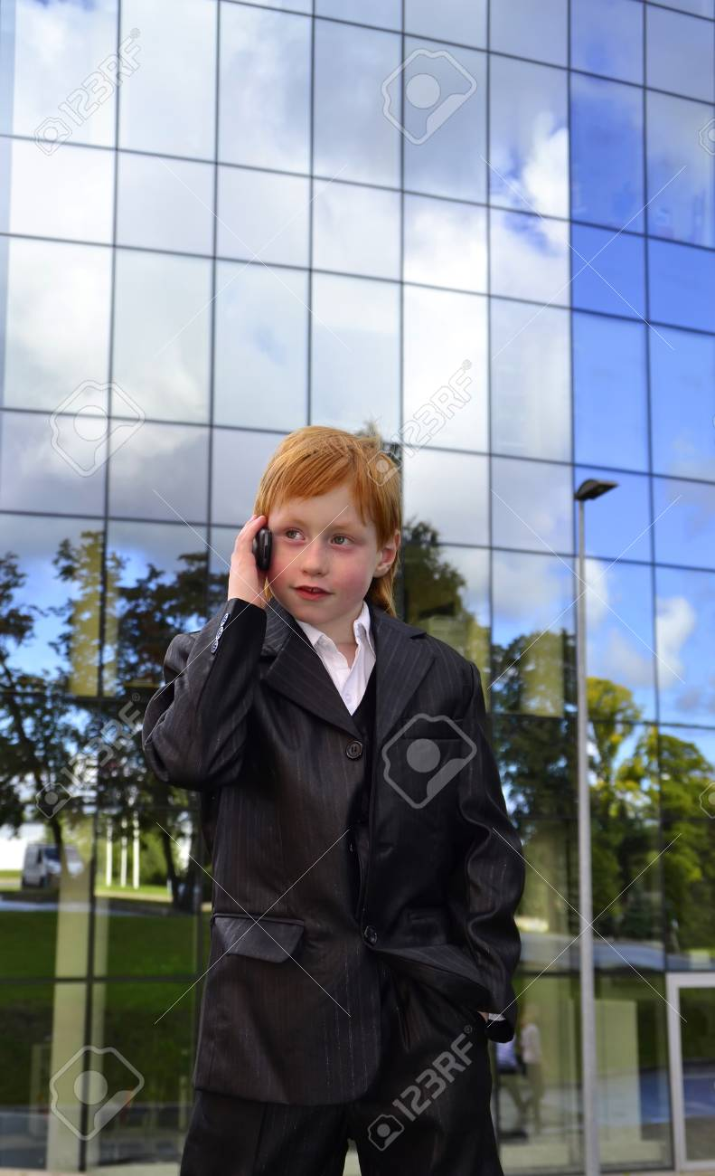 Smart boy talking by phone in front of an office building Stock Photo - 10551848