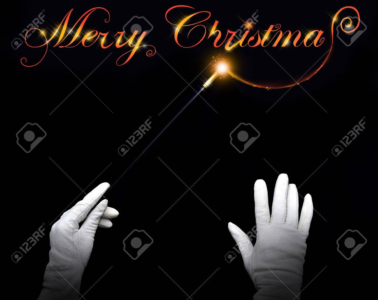 Wizard hands drawing 'Merry Christmas' on a black background Stock Photo - 11143224
