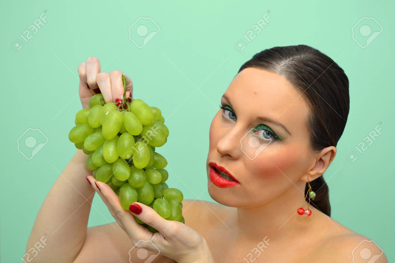 Pretty woman intending to eat bunch of grapes Stock Photo - 12466796