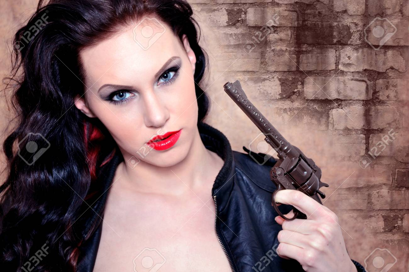 Portrait of a young woman holding the pistol Stock Photo - 13581793