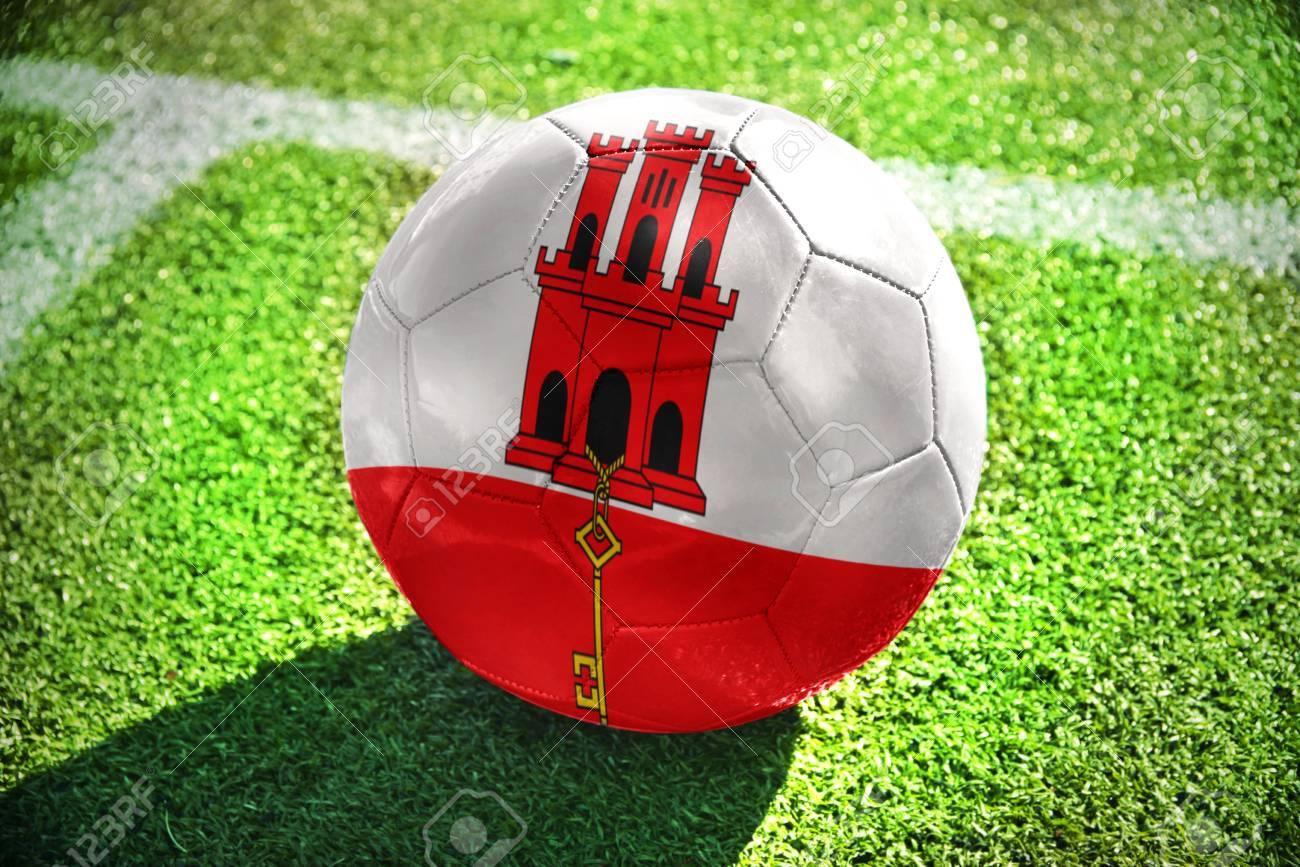 248c6feb15005 Foto de archivo - Pelota de fútbol con la bandera nacional de Gibraltar se  encuentra en el campo verde cerca de la línea blanca