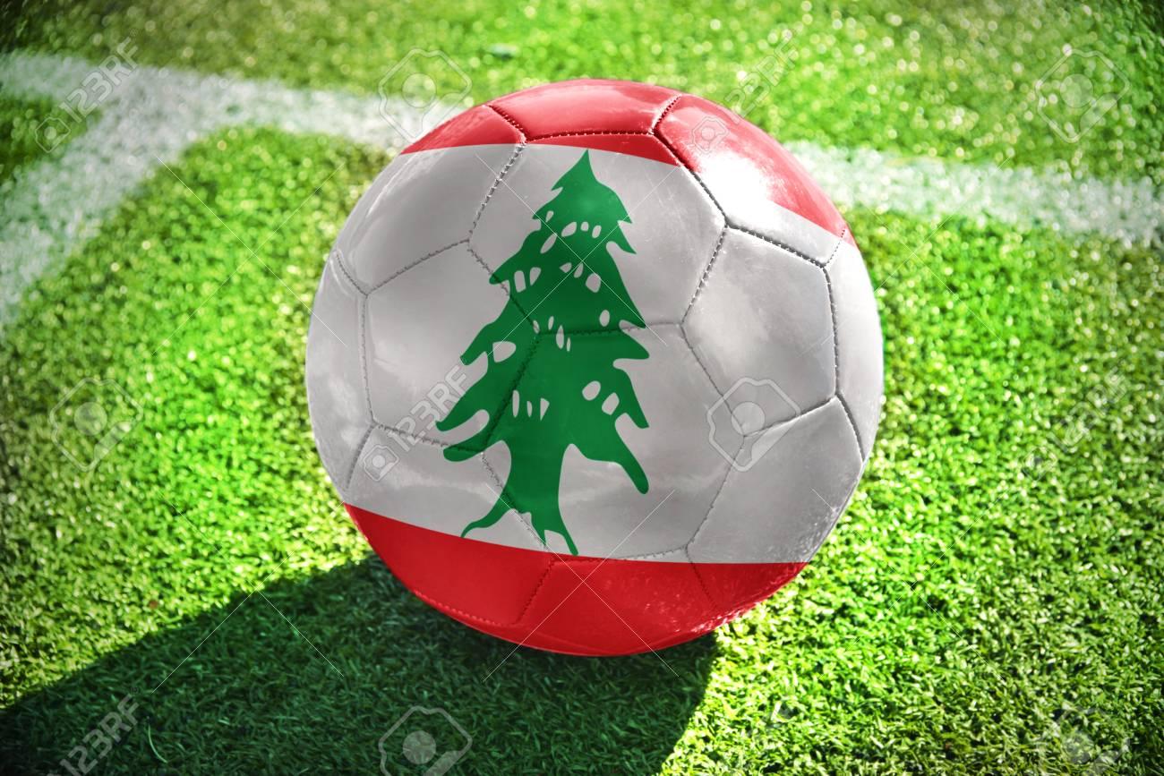 6e1a40ce4ceb5 Foto de archivo - Pelota de fútbol con la bandera nacional de Líbano se  encuentra en el campo verde cerca de la línea blanca