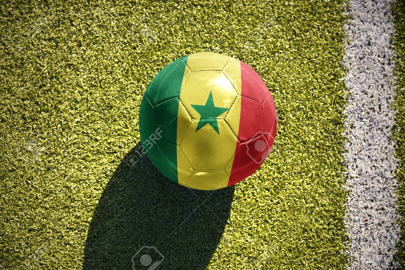 06937b6df40 football ball with the national flag of senegal lies on the green field  near the white