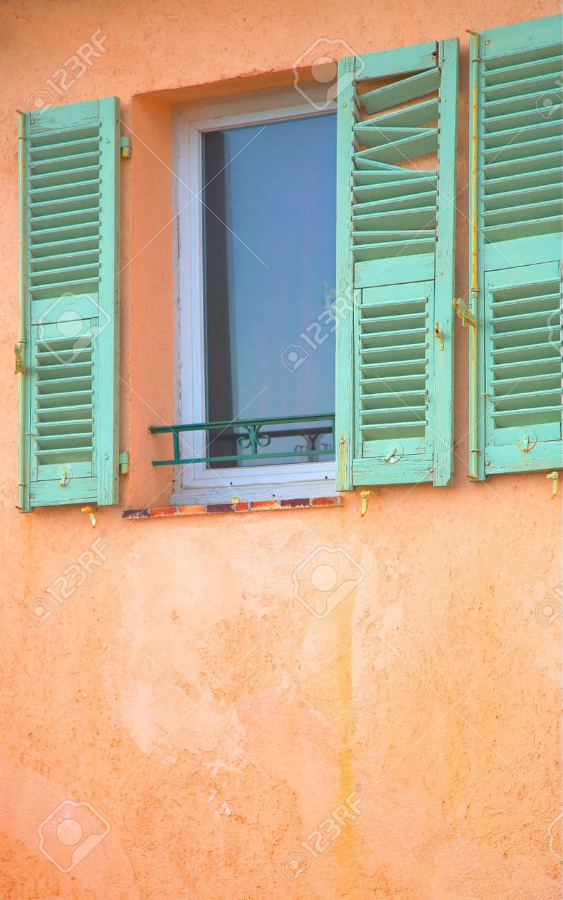 Old Green Shutters With Rusted Stains Framing A Small Window