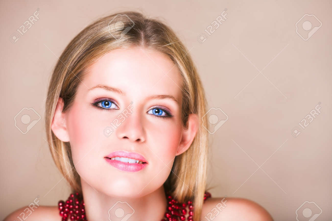 Blond teenage girl with loose straight hair on beige background with red shiny necklace and soft smile. Natural make-up,  has skin texture. Stock Photo - 2123493