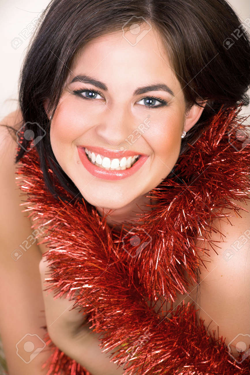 Beautiful woman with long brown hair, blue eyes with red shiny tinsel Stock Photo - 2180181