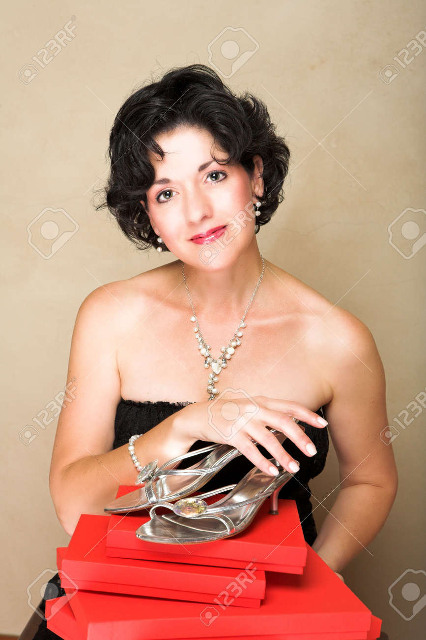 Woman in lace black dress with short curly hair, wearing pearls, holding shoes on top of red gift boxes Stock Photo - 2180160