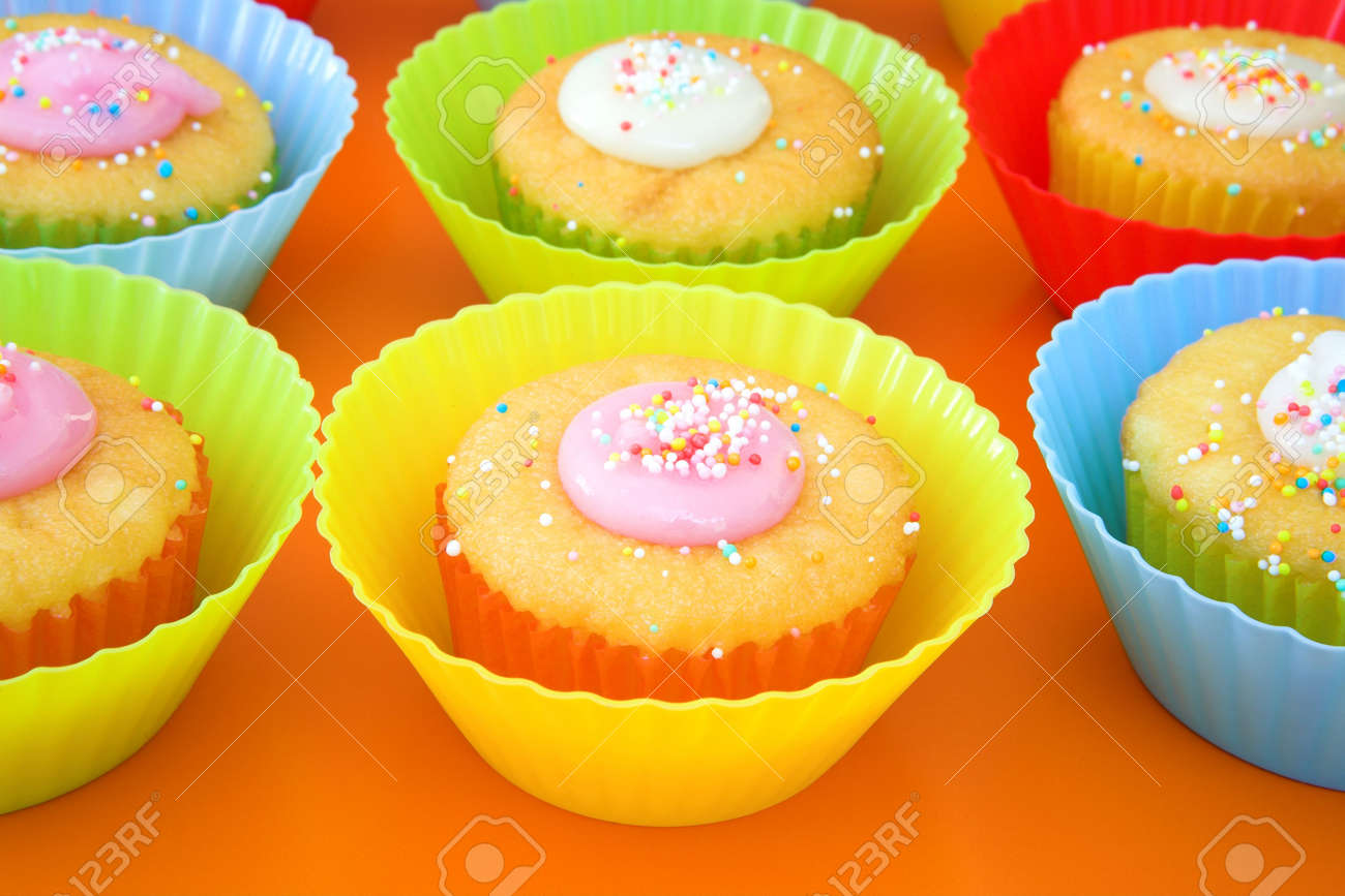 Display of small party cakes with icing sugar in bright plastic cups. Focus on middle cake Stock Photo - 2368078