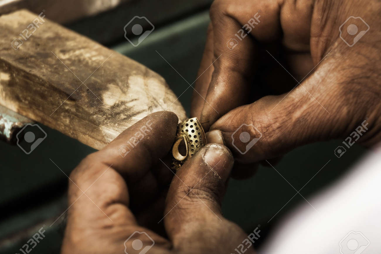 Goldsmith holding an unfinished 22 carat gold earring in his hard working hands. Shallow DOF - focus on earring. Fine gold dust on hands Stock Photo - 2733957