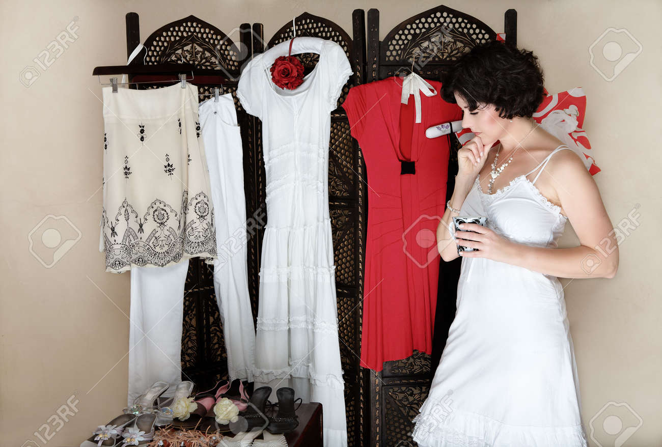 Woman in her 30s-40s standing next to a collection of shoes and other hanging clothes � thinking Stock Photo - 2949830