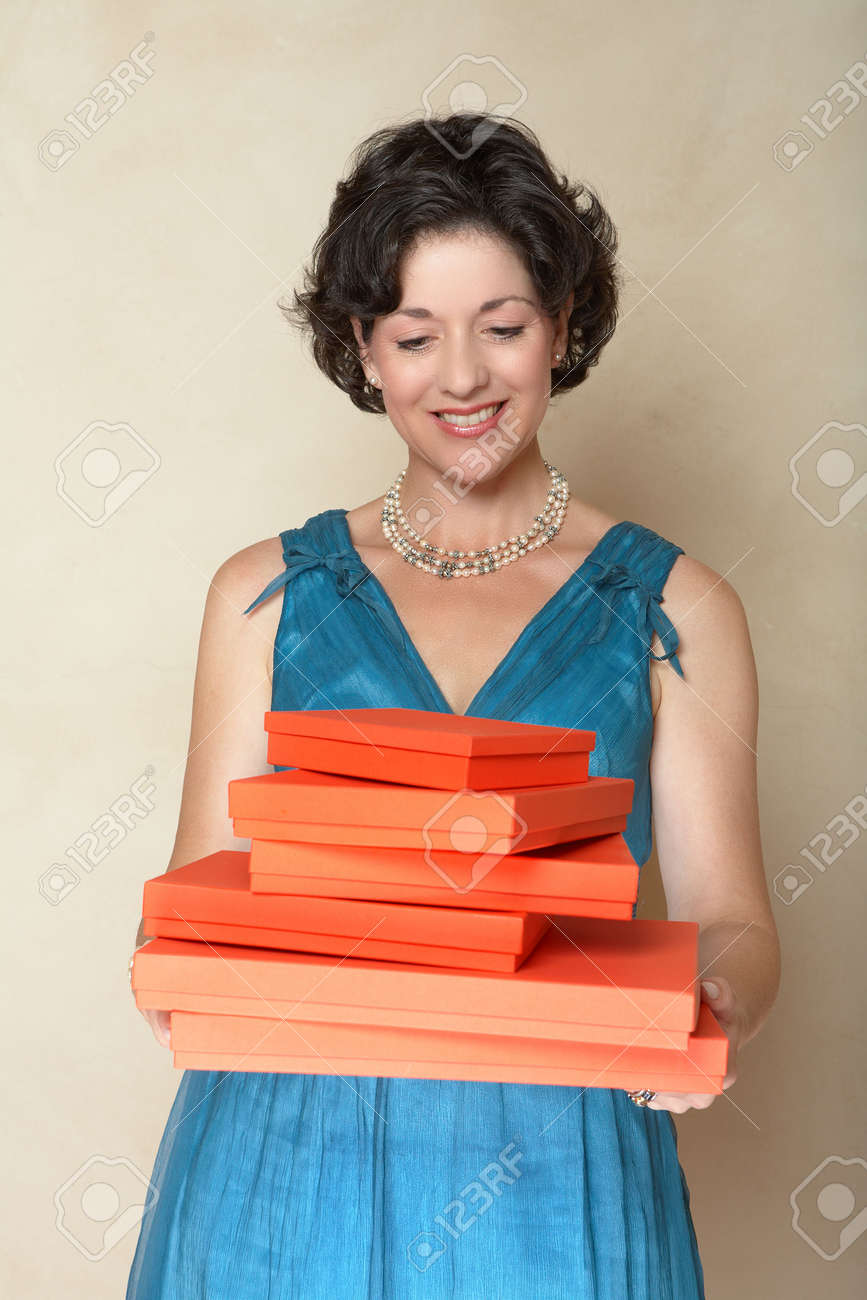 Beautiful woman in blue fashion dress holding a stack of red gift boxes Ð smiling in her mid 30s Stock Photo - 2949836