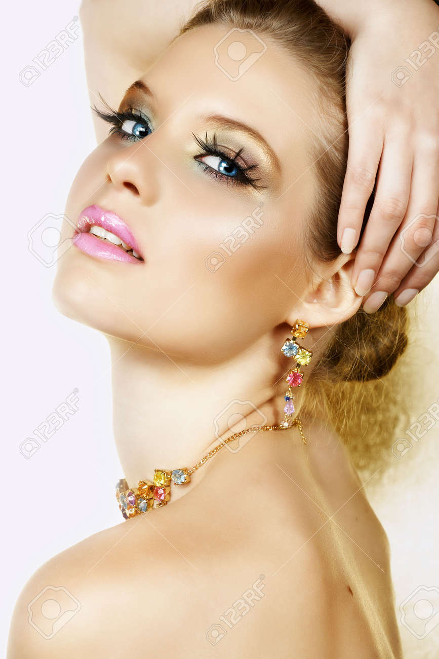 Beautiful blond woman with long lashes and colourful stones necklace and earrings and seductive smile � not isolated Stock Photo - 3140871