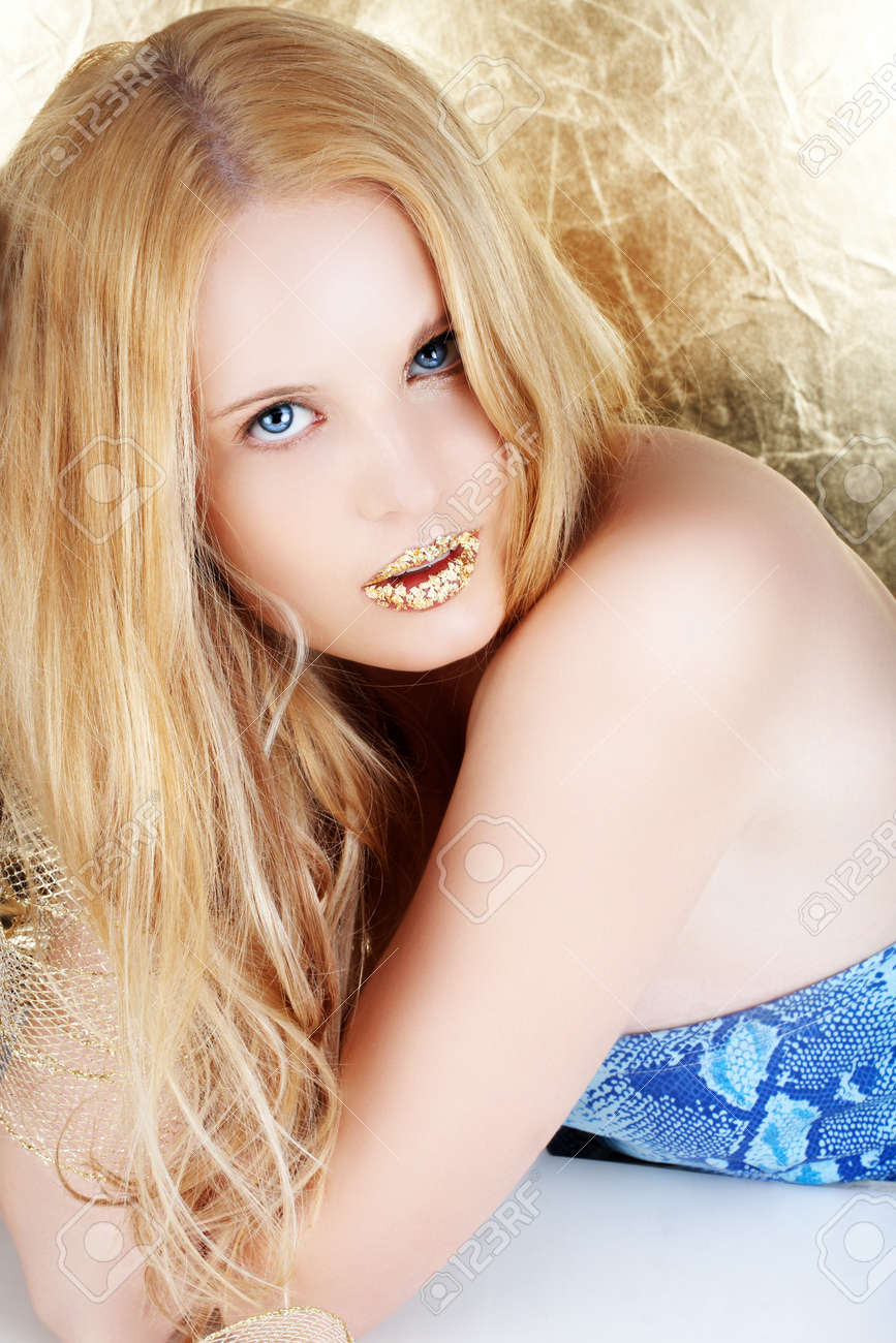 Beautiful young blond woman with long hair and gold leaf lips on golden background Stock Photo - 4241425
