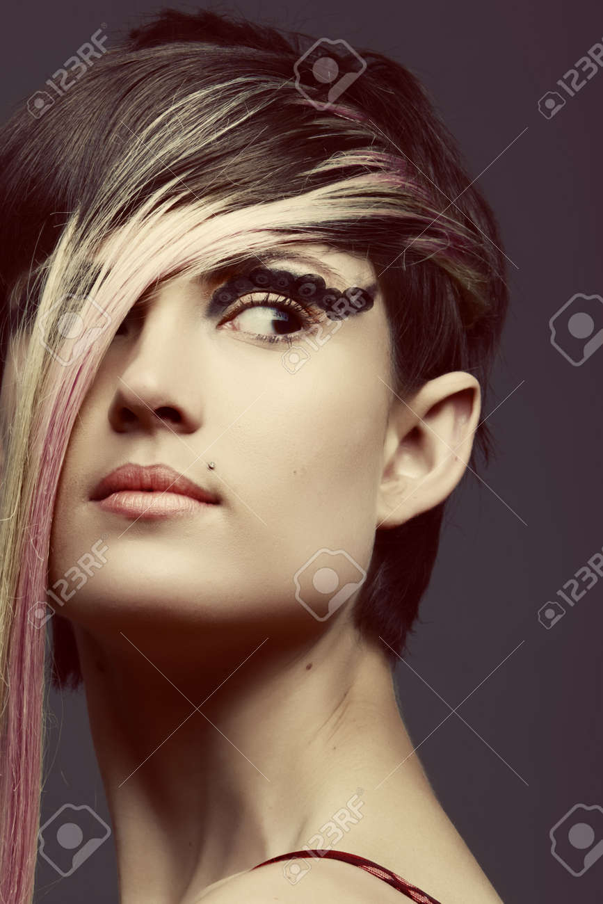 emo girl with long blond fringe and cat eye make up piercing