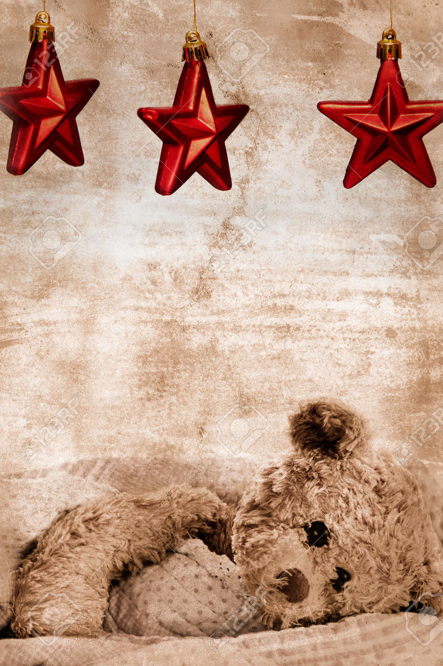 teddy bear in blanket under three Christmas red stars on grunge background with copy space - generic toy with slightly modified appearance Stock Photo - 8216000