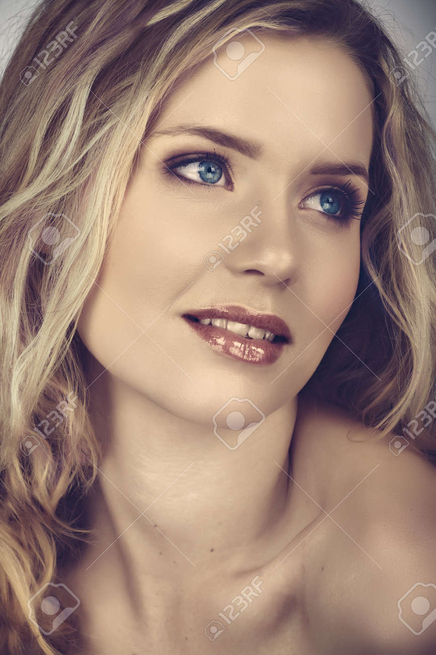 beautiful young woman with long curly blond hair and natural make-up smiling happily with cross process effect from 16 Bit RAW Stock Photo - 8744656