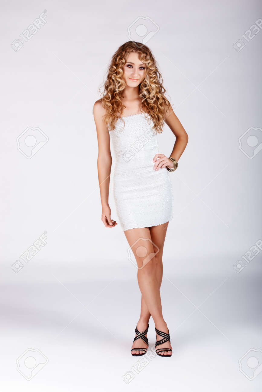 Beautiful young blonde woman with long curly hair in fashion white minidress on studio background. Stock Photo - 10012105