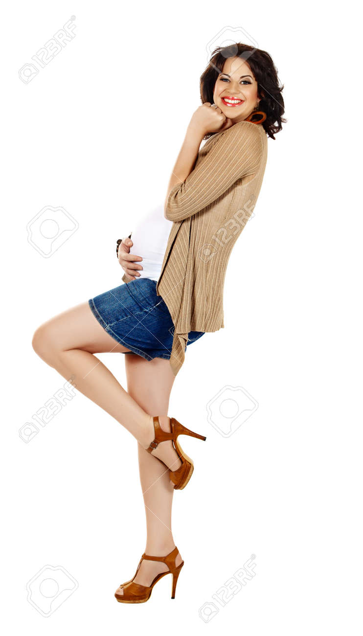 beautiful eight months pregnant brunette woman wearing fashion shorts and high heels over white studio background Stock Photo - 10327986