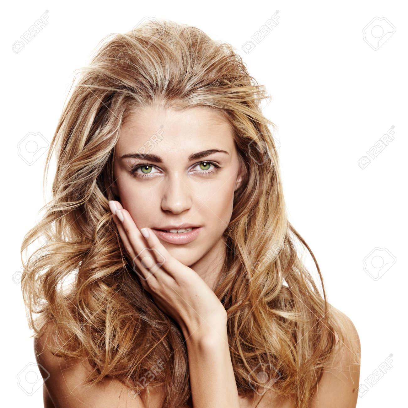 belle femme souriante avec de longs cheveux blonds bouclés et maquillage naturel sur fond blanc toucher son visage Banque d'images - 12470207