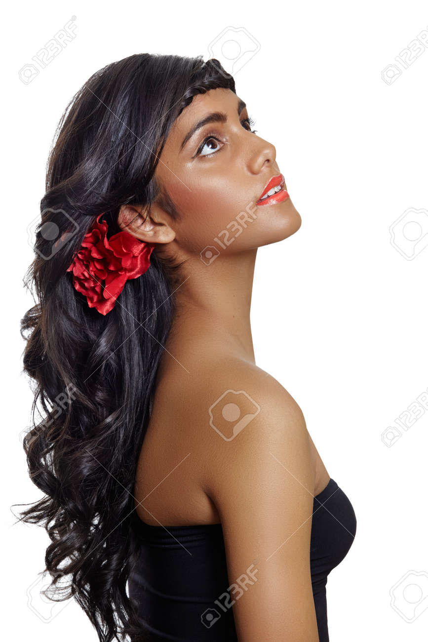 portrait d'une belle jeune femme bronzée à long brun cheveux bouclés et fleur rouge, du rouge à lèvres rouge et robe noire, assise de profil sur fond blanc Banque d'images - 12470277