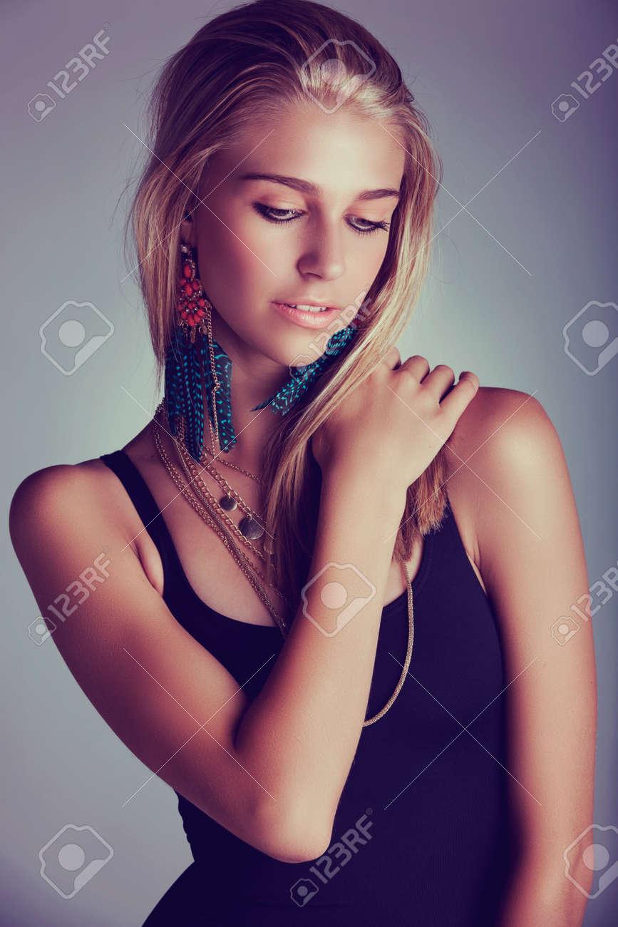 belle jeune femme blonde aux cheveux longs portant de longues boucles d'oreilles corail plume - abattu que le portrait discret avec effet rétro. Banque d'images - 14683798