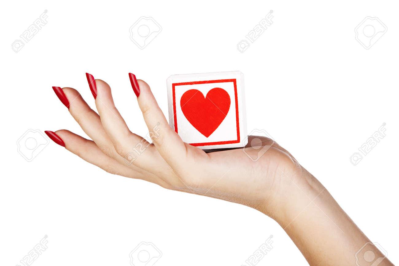 Plan rapproché de la main jeune femme avec de longs clous s rouges bloc de maintien avec le coeur rouge Banque d'images - 14679534