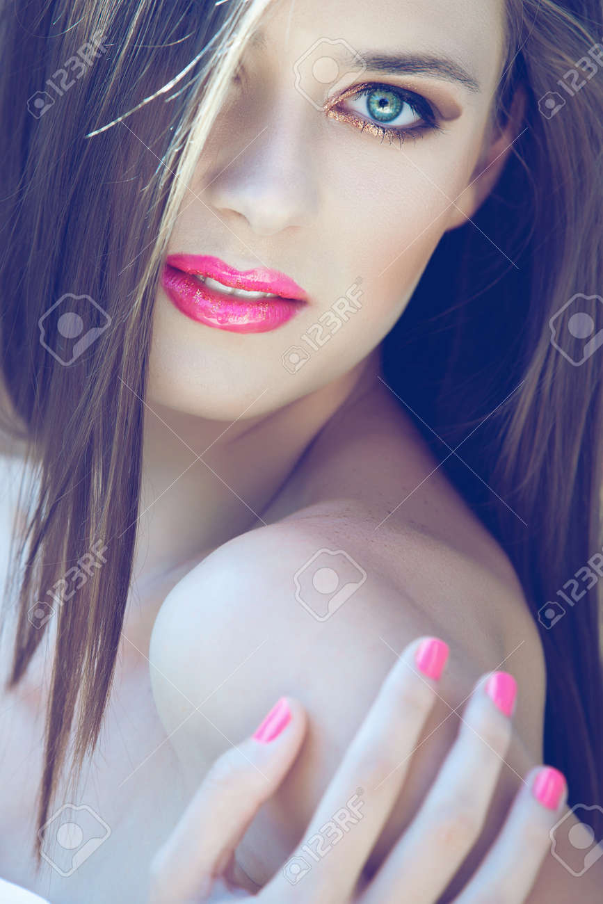 portrait of a beautiful woman with long hair and bright pink lips wearing glitter gold eyeshadow Stock Photo - 14683791