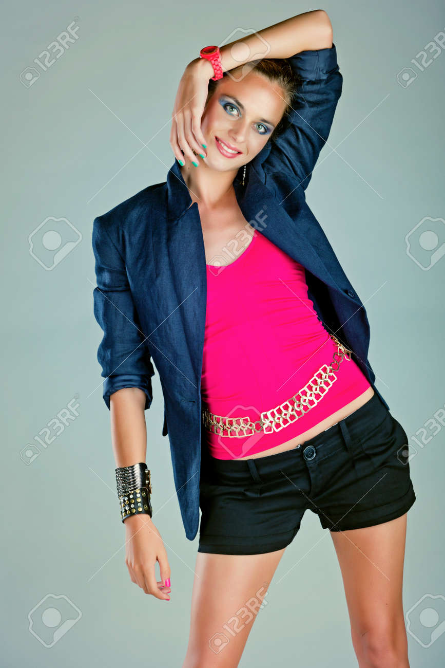 beautiful young woman with dramatic make-up and green pink manicure wearing shorts, dark navy blue linen jacket and pink neon watch on blue background Stock Photo - 14683786