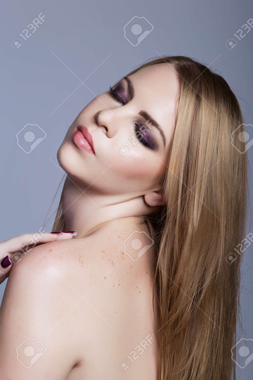 beautiful woman with purple eyeshadow on closed eyes and long blond hair over her shoulder against the blue studio background Stock Photo - 14683785