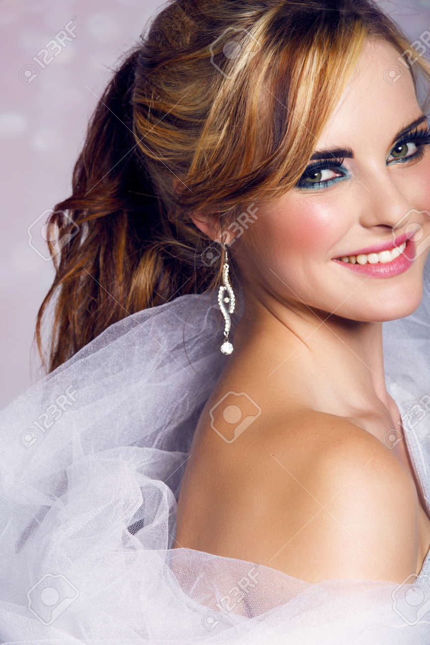 happy beautiful bride with long blond hair in ponytail waring artistic smoky eyeshadow and smiling on bokeh background. Stock Photo - 14683793