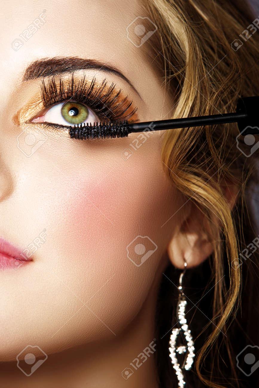 portrait of beautiful woman with smoky gold eyeshadow and long false eyelashes applying mascara with a wand Stock Photo - 14683800