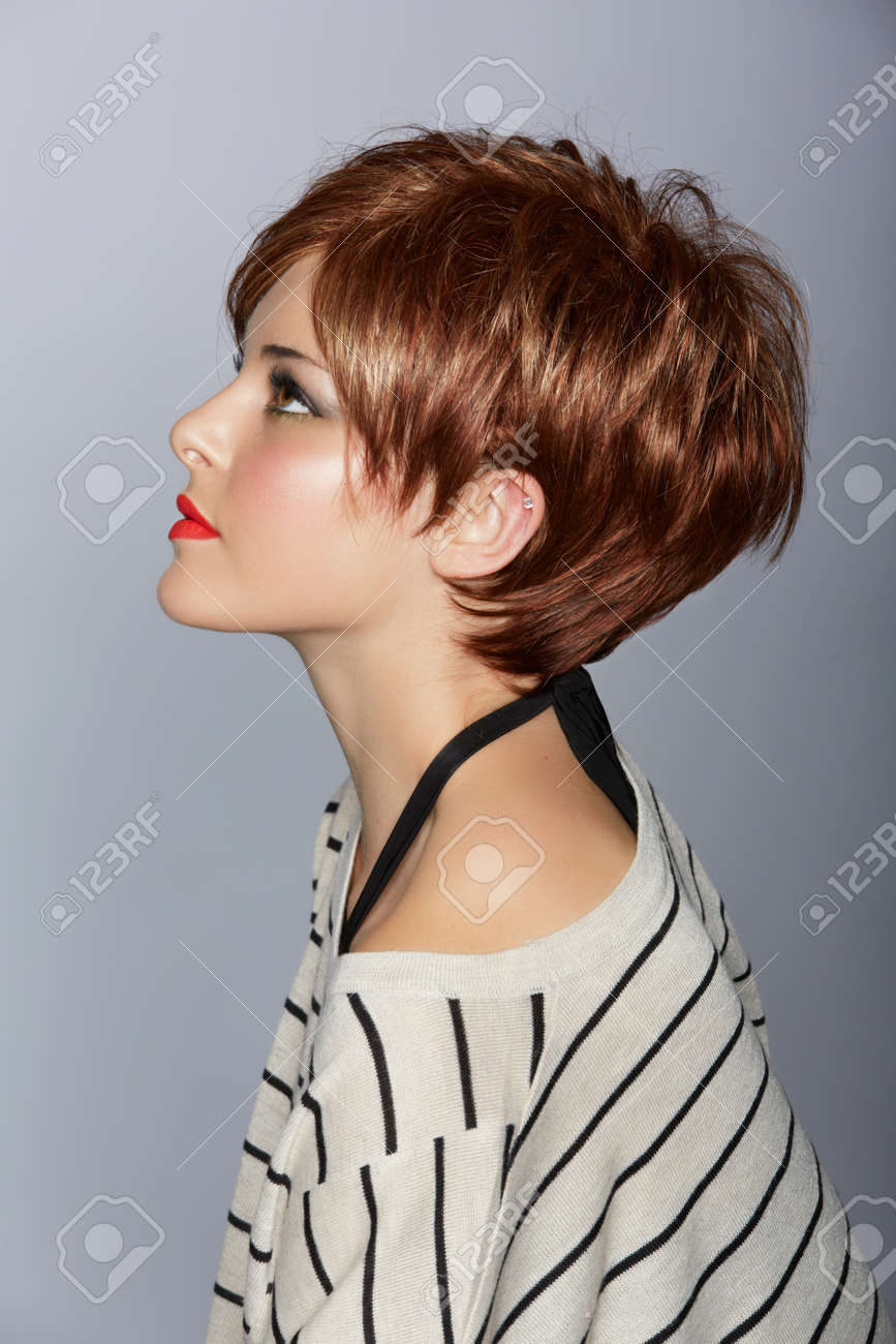 profile of a beautiful woman with red lips and short feathered red hair in modern bob over studio background Stock Photo - 14692501