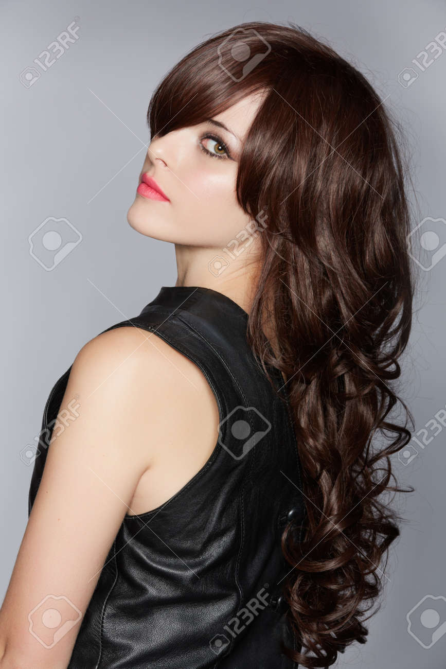 woman with long brown curly hair with healthy shine, wearing a leather dress over a studio background Stock Photo - 14683839