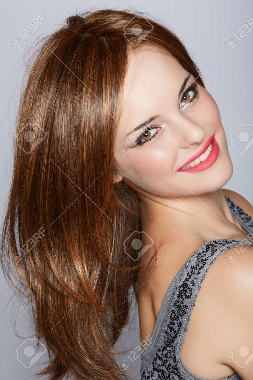 portrait of a beautiful woman with long brown hair looking over her shoulder with a smile over a studio background Stock Photo - 14683840