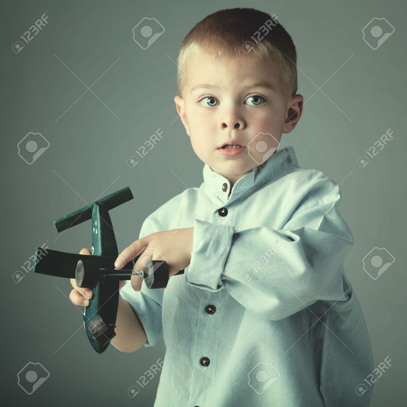 young 3 year old boy wearing blue shirt playing with wooden toy airplane in his hand on blue studio background Stock Photo - 14683811